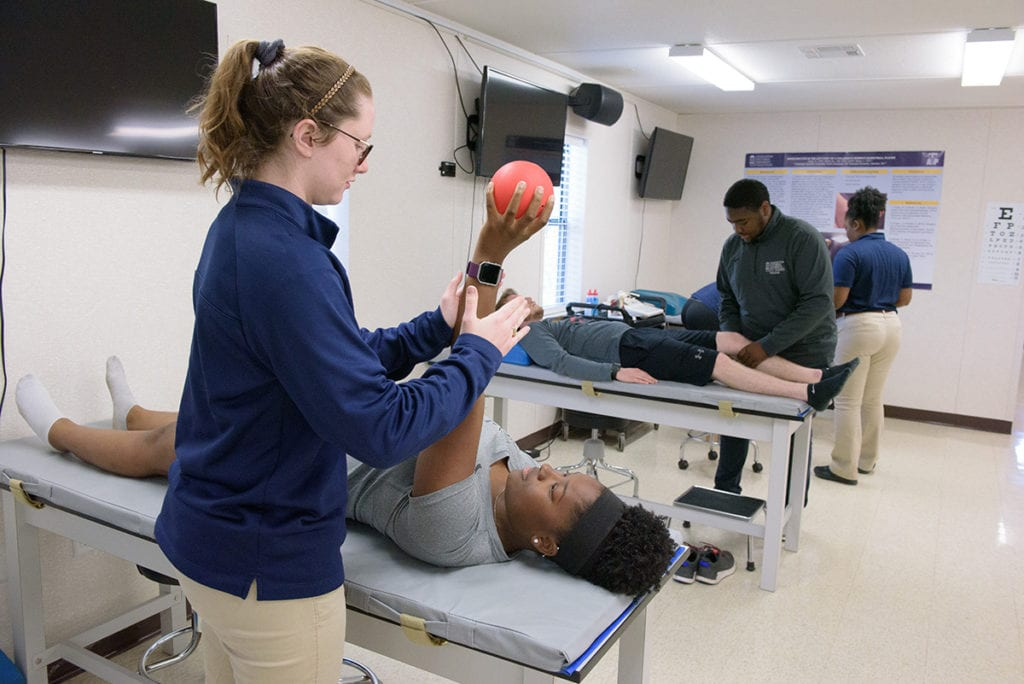 Athletic training students working on other students in a classroom lab.
