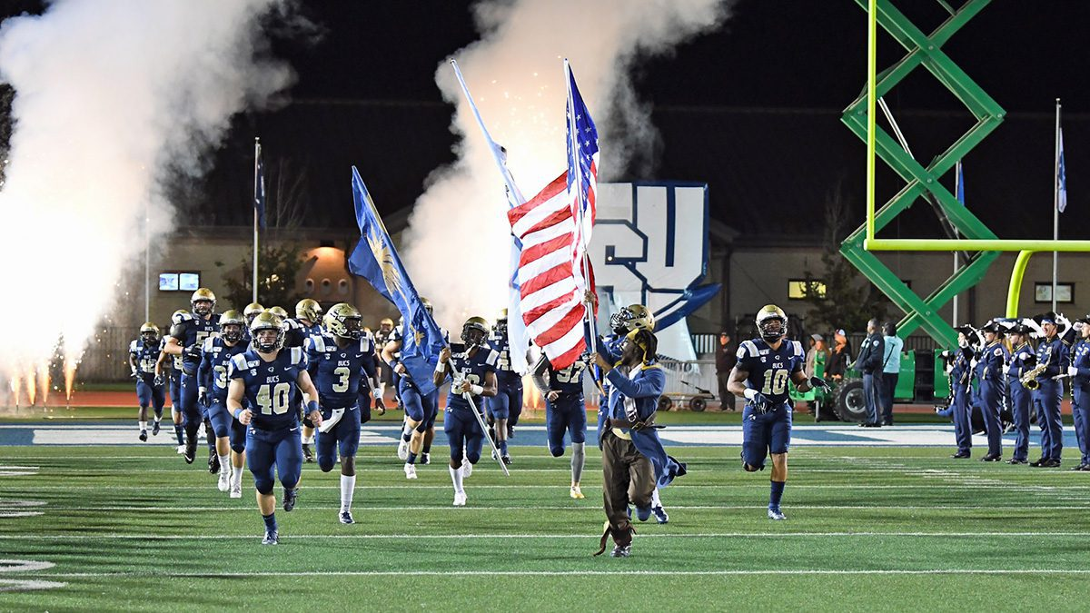 CSU's football team running onto the field pre game with smoke and the CSU logo behind them.