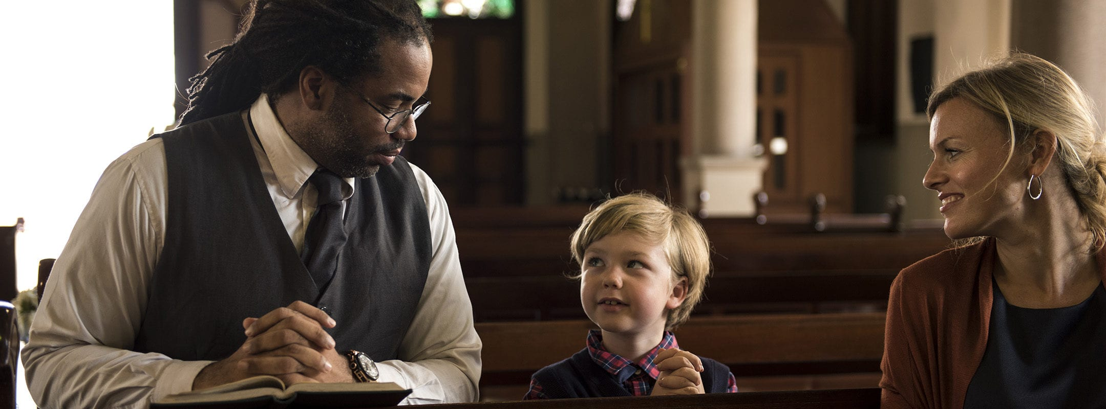 A mom and her son in a church pew speaking with a minister
