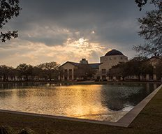 The Science building with a sunset reflecting off the reflection pond.