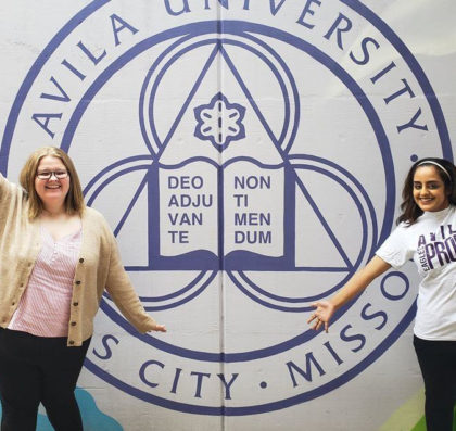 Picture of two young women posing in front of a wall with Avila University seal.