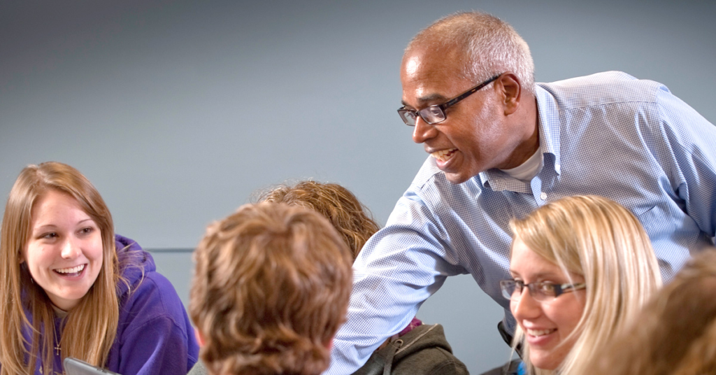 Avila Professor Daniel George in class with a group of students