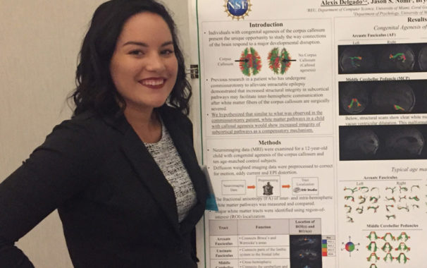 Alexis Delgado standing in front of research poster
