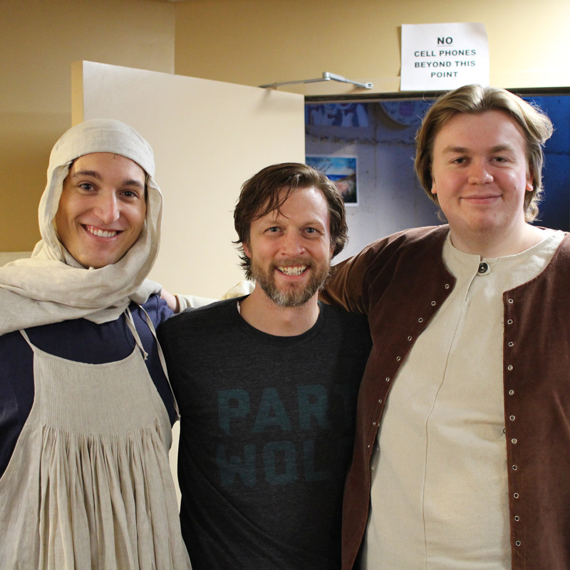 Three Avila students and faculty standing back stage at theatre production