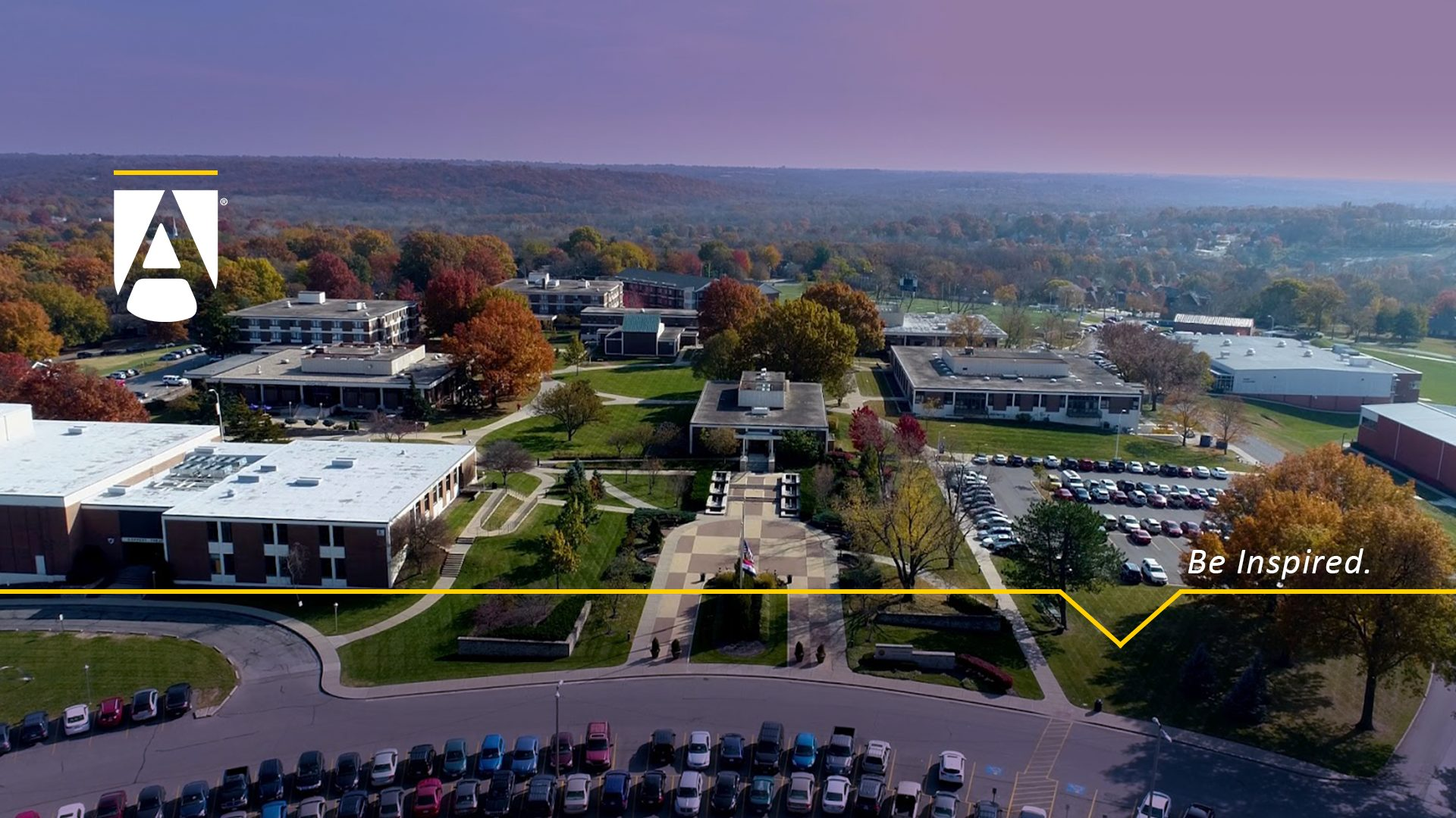 "Aerial view of campus looking south with the JHOP Plaza in the foreground. Text says ""Be Inspired."""