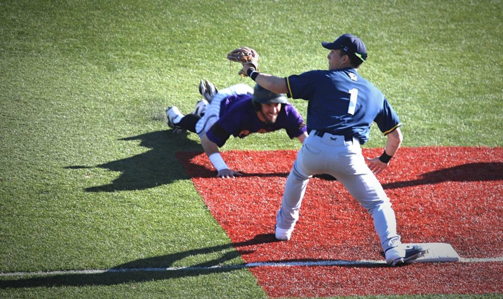 Avila players sliding head-first into third base to beat the tag