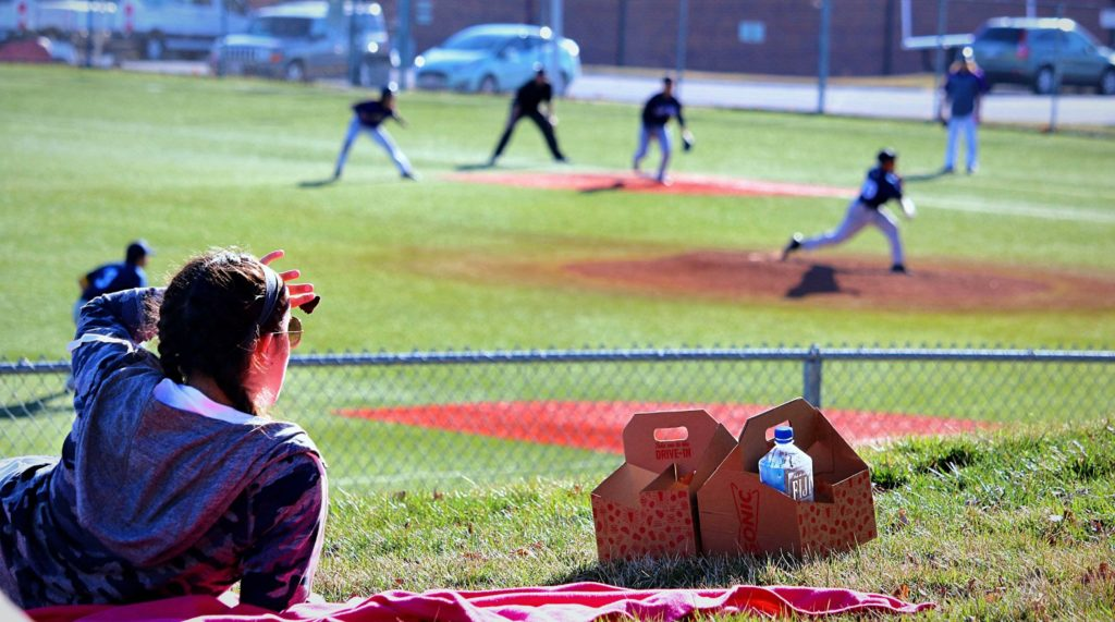 Fan sitting on the hill watching a baseball game