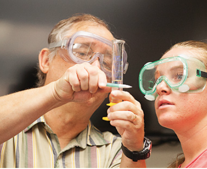 Avila professor and student measuring a liquid in a test tube