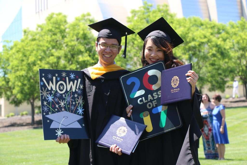 Two class of 2017 graduates in their cap and gowns holding their diplomas and signs
