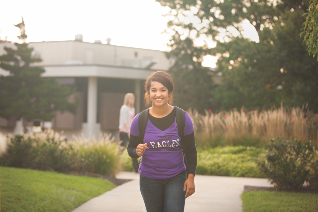 Avila student with backpack walking toward camera on campus