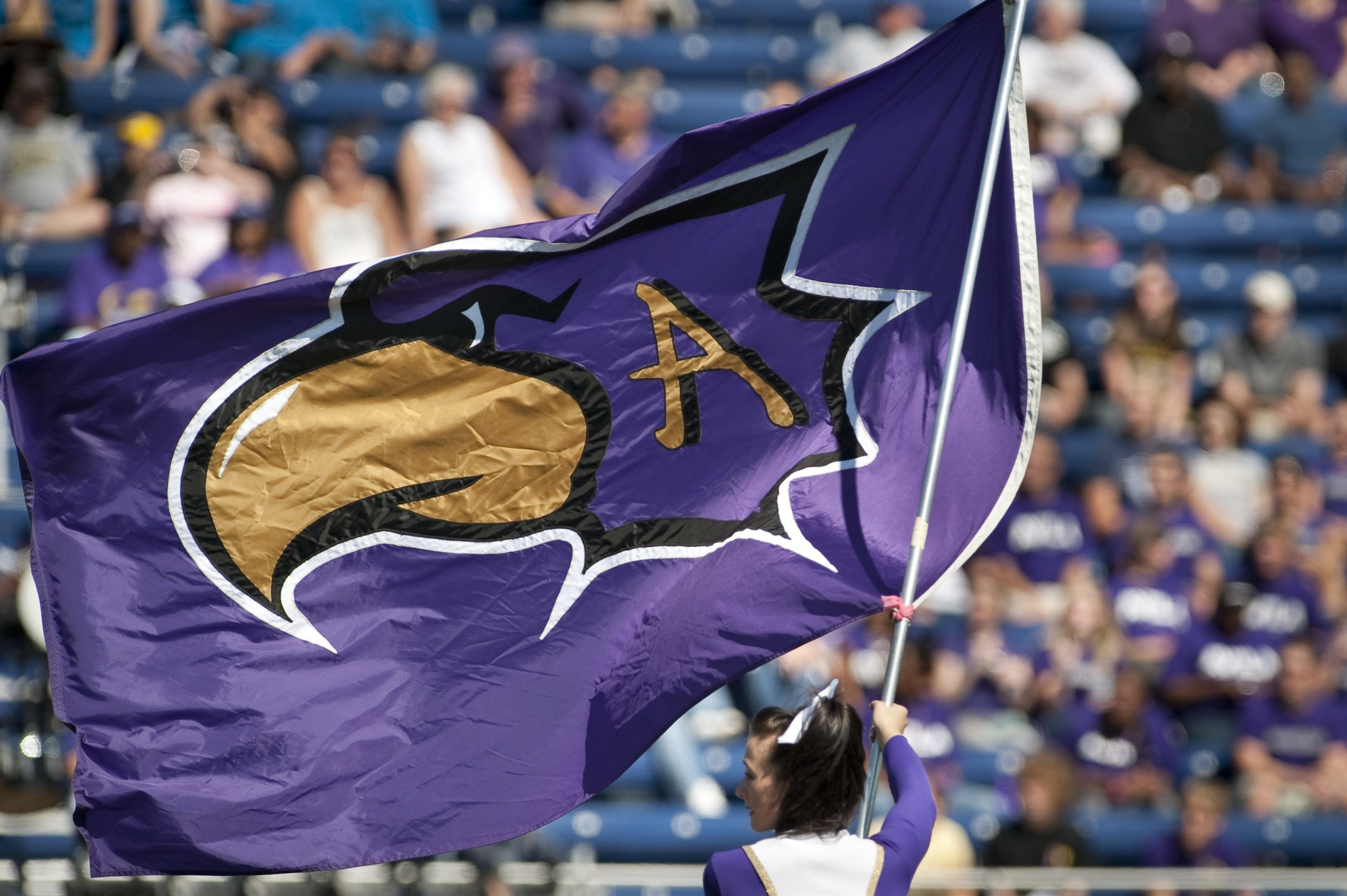 Avila University Eagle logo flag being waved at football game by cheerleader