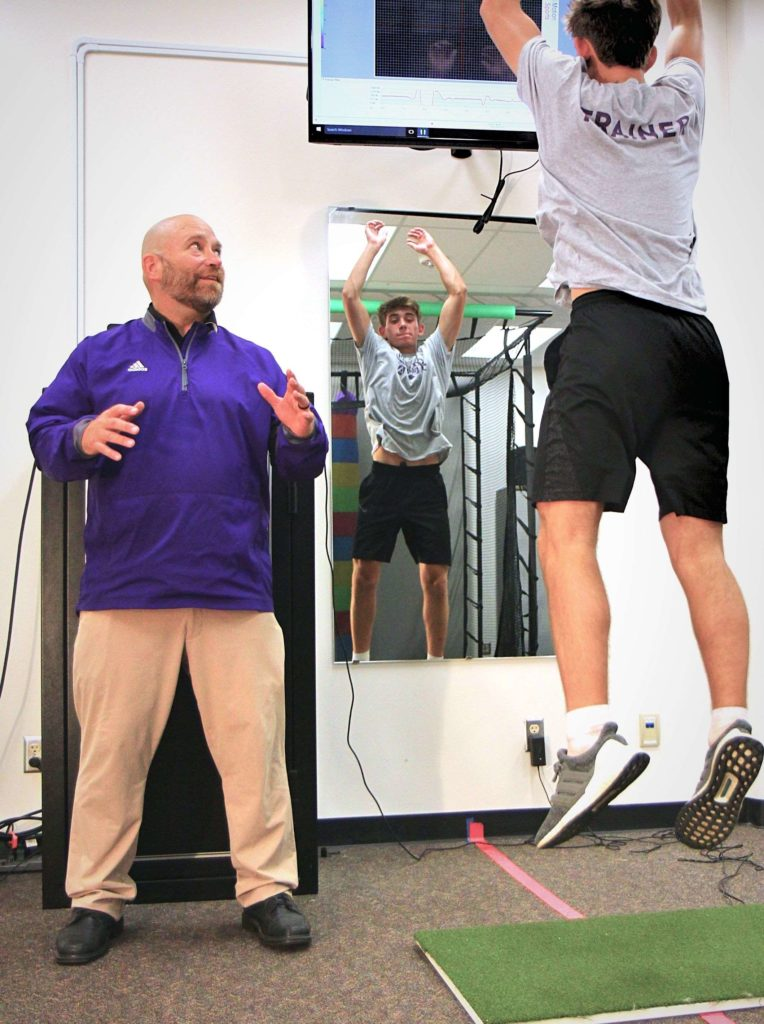 Professor Gerald Larson instructing Kinesiology student who is jumping in the lab