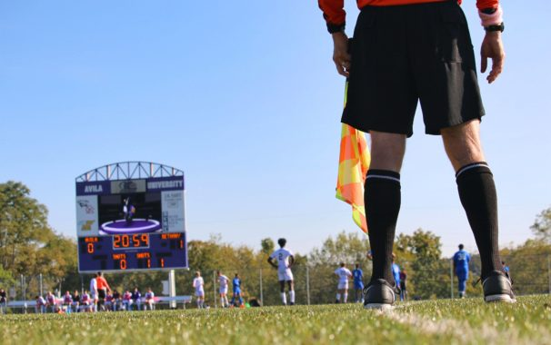 Ground level shot of a men's soccer match, the referee's legs are in the foreground