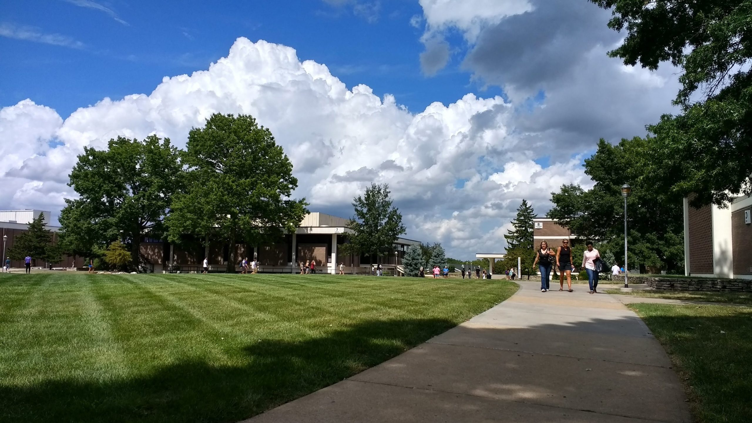 Wide view of the campus Quad with students walking along the sidewalks