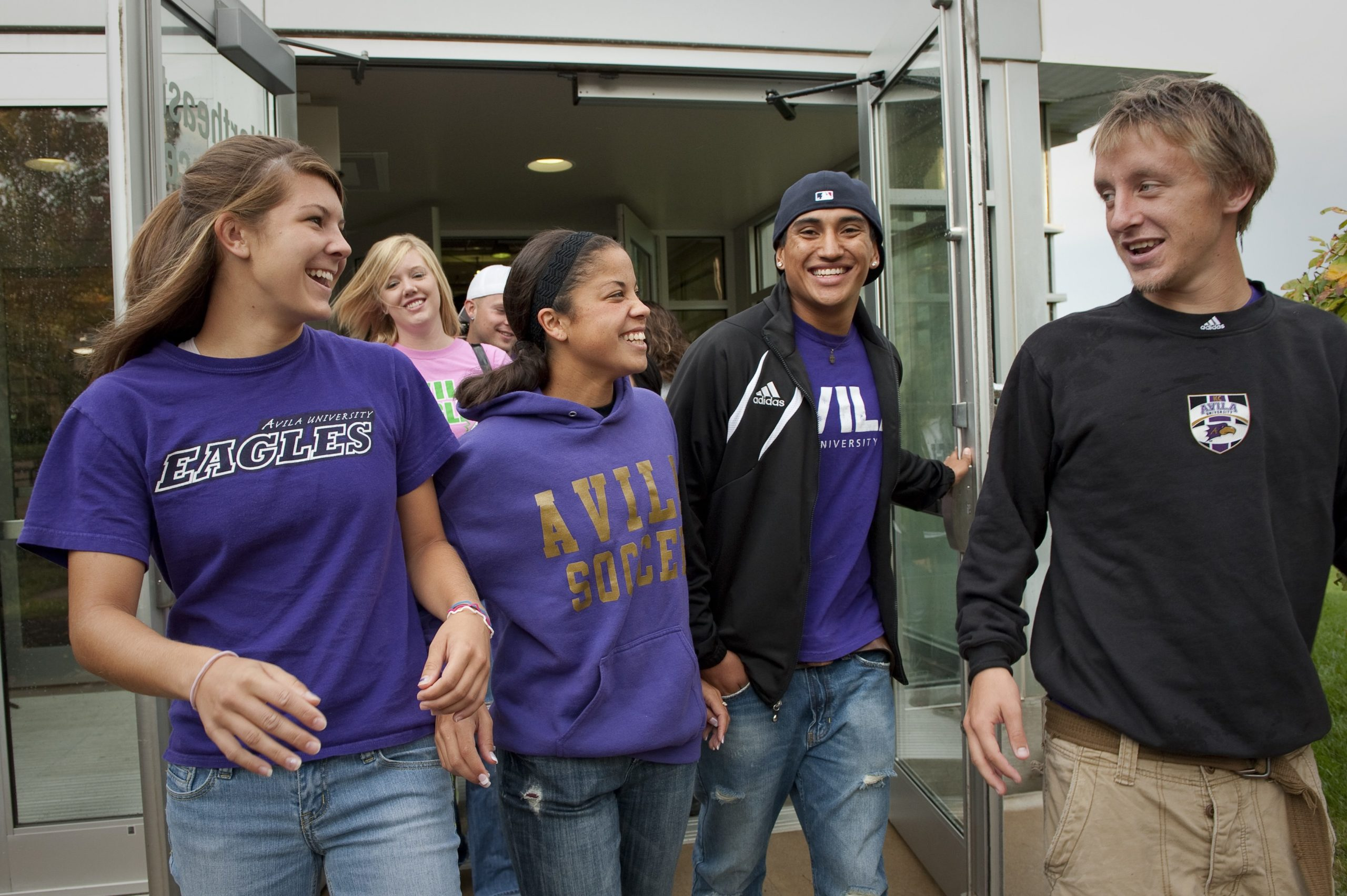 Group of four Avila students exiting Mabee Fieldhouse doors