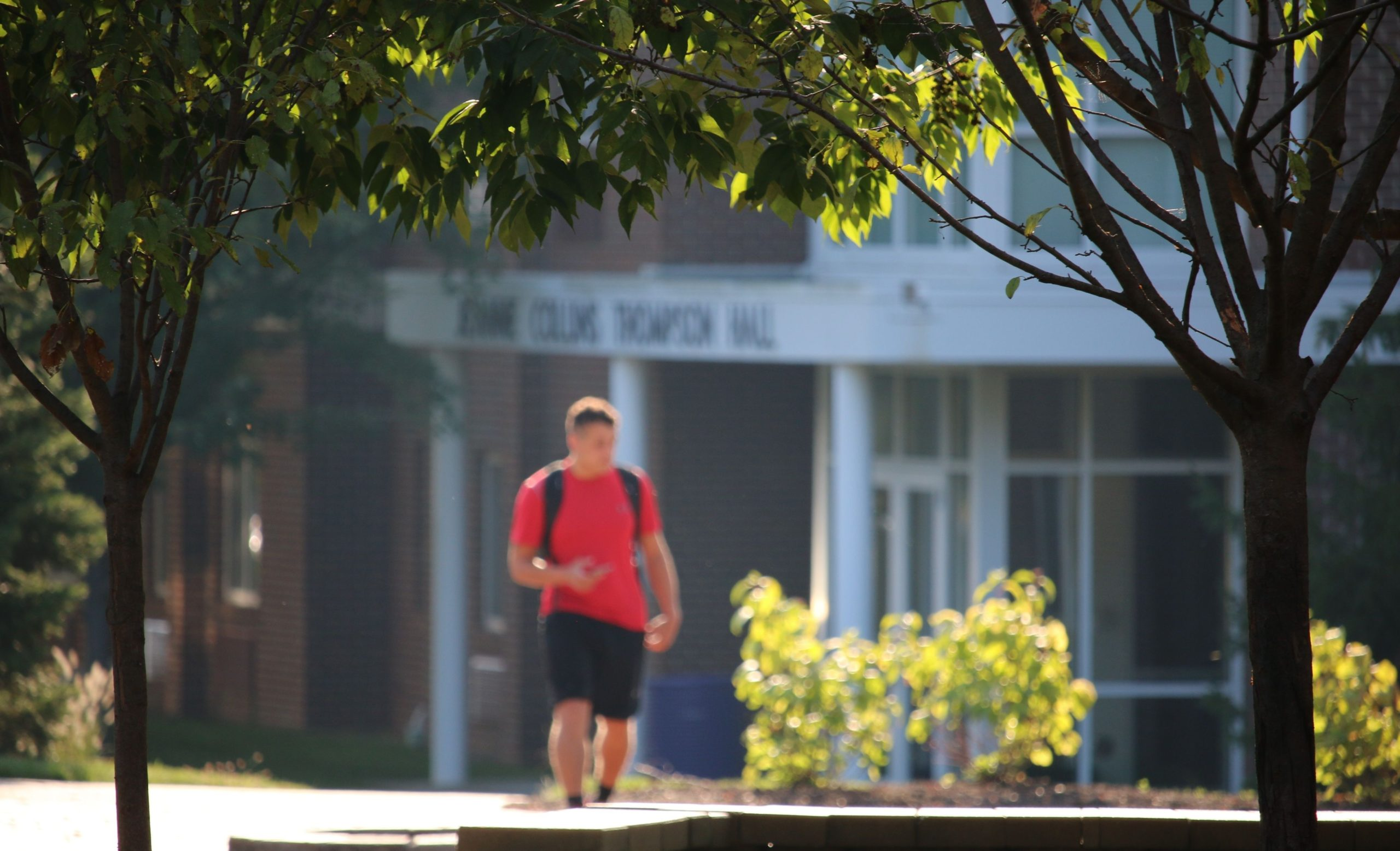 Male student walking in front of Thompson Hall
