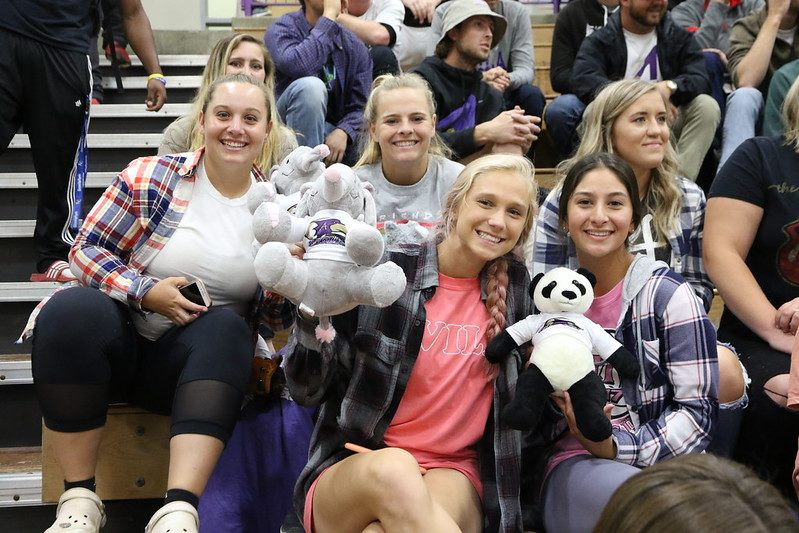 Crowd of students sitting in the Mabee Fieldhouse stands holding stuffed animals