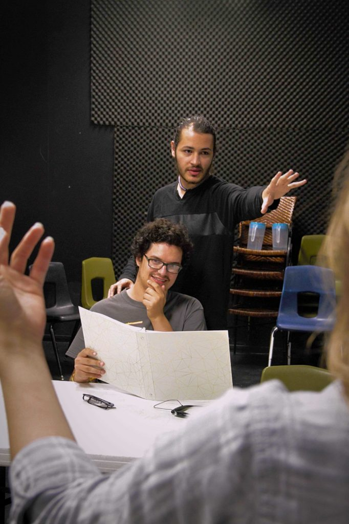 Two students in the theatre rehersal room directing a third student