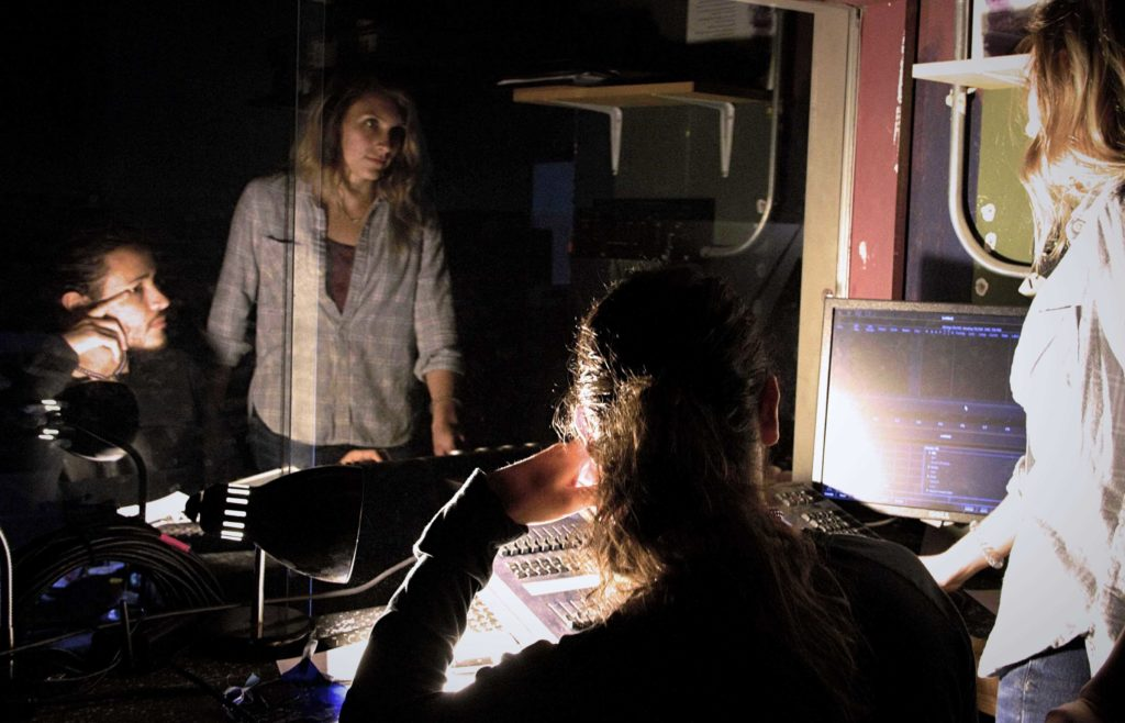 Two theatre students in the sound booth area of the Goppert Theatre