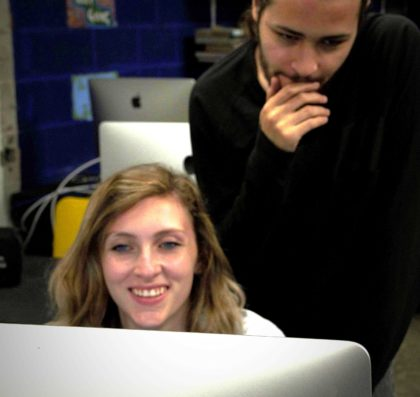 Two theatre students pondering a stage design on a computer screen