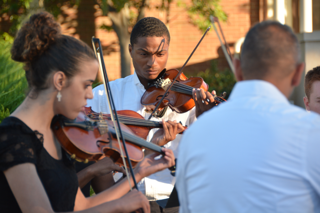 Close up of students playing the violin outside Blasco Hall