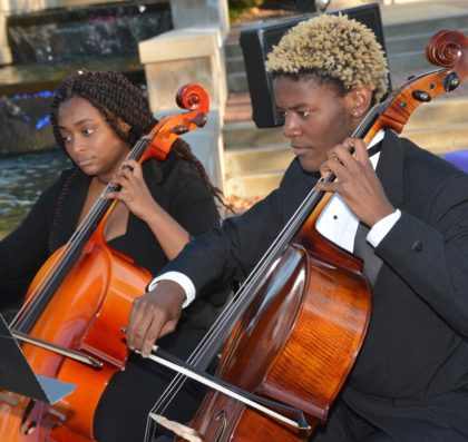 Two Avila cellos players perform outside Blasco Hall
