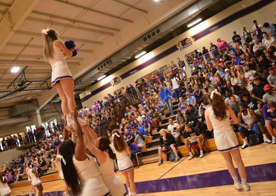 Cheerleaders performing a stunt inside the Mabee Fieldhouse in front of a packed house