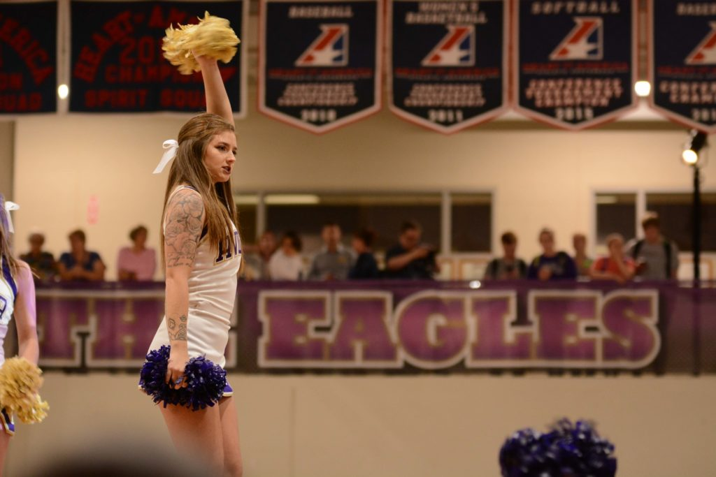 Close up of a cheerleader with poms inside Mabee Fieldhouse