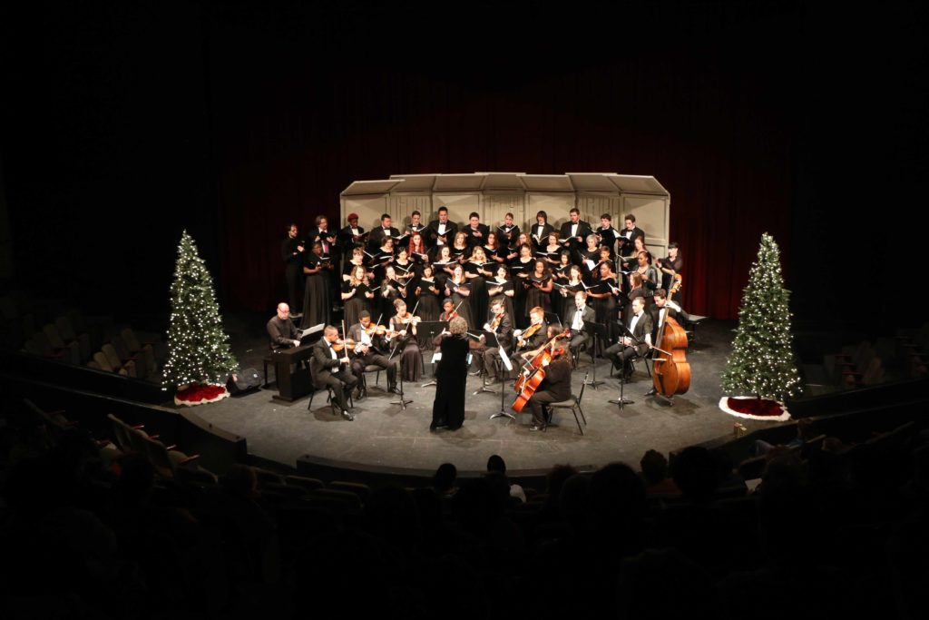 Avila choir and string performers on on the Goppert Theatre stage during a Christmas concert