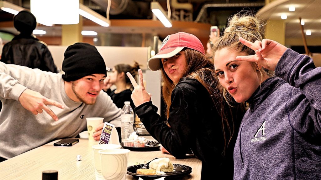 Three students posing inside the Marian Center dining hall