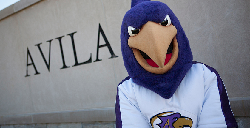 The Avila mascot, Dom the Eagle, standing in front of Avila campus sign