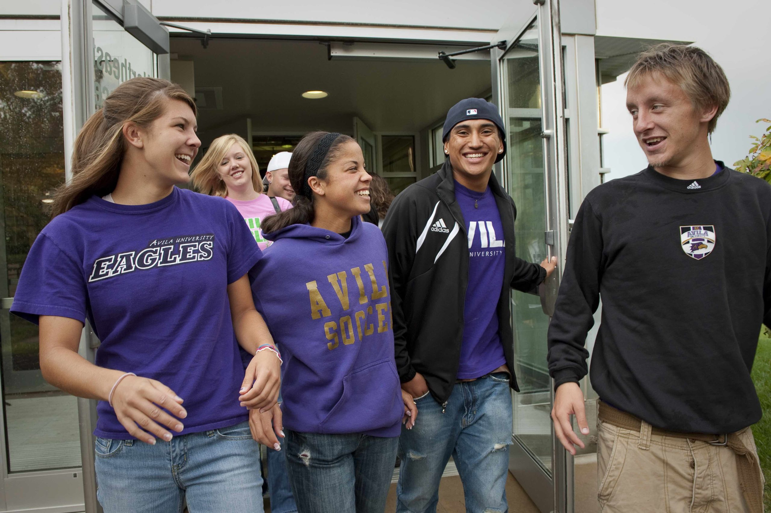 Group of four students exiting the doors of Mabee Fieldhouse