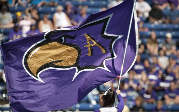 Cheerleader waving an oversized Avila Eagles flag during football game