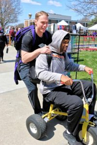 Two students riding a giant tricycle during the campus carnival