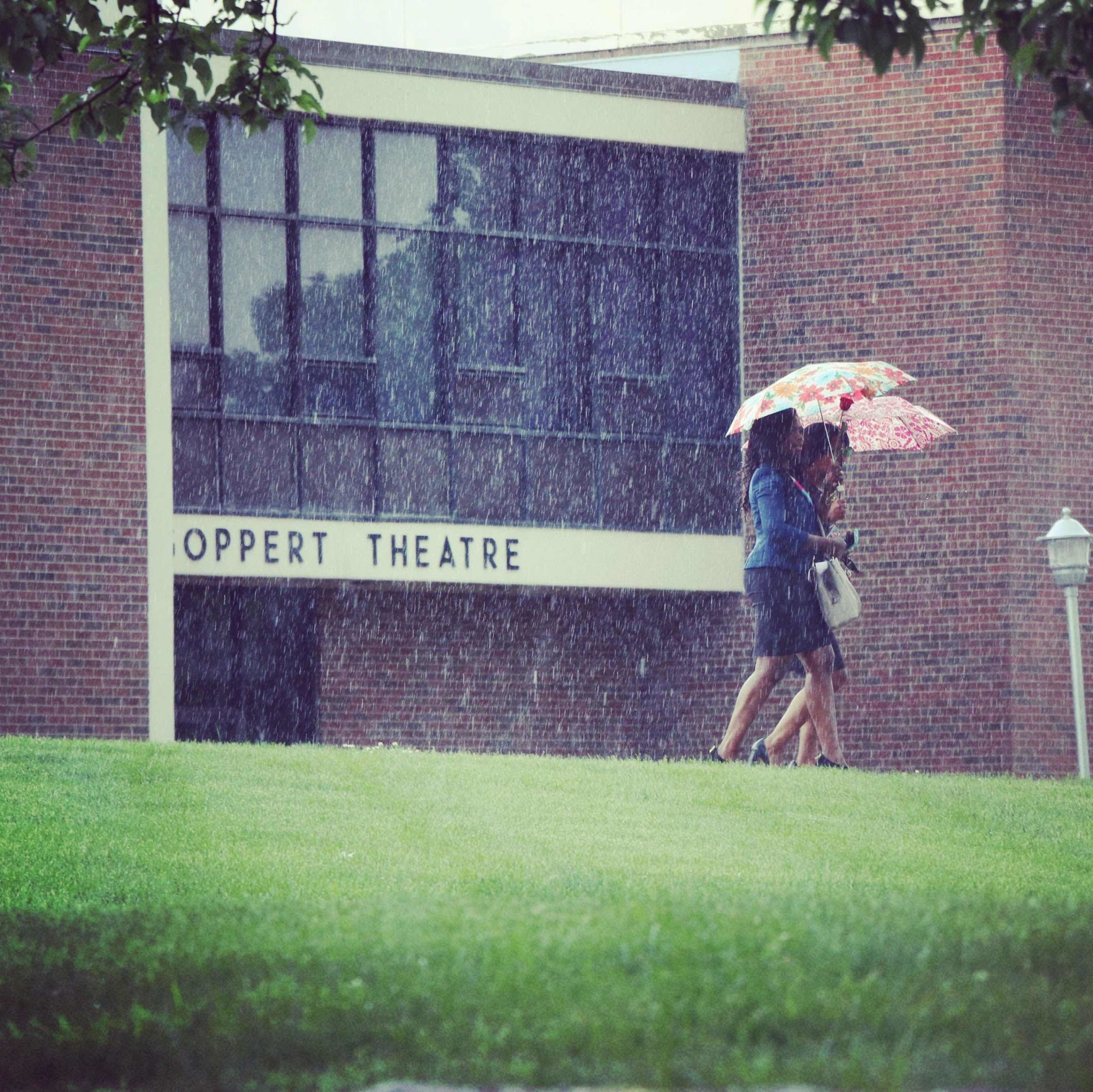 Two students holding umbrellas and walking in the rain past the Goppert Theatre entrance.