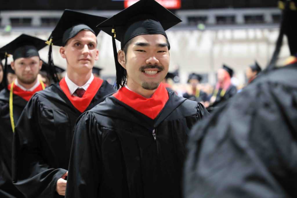 Male student smiles at camera while standing in a line of four students in caps and gowns.