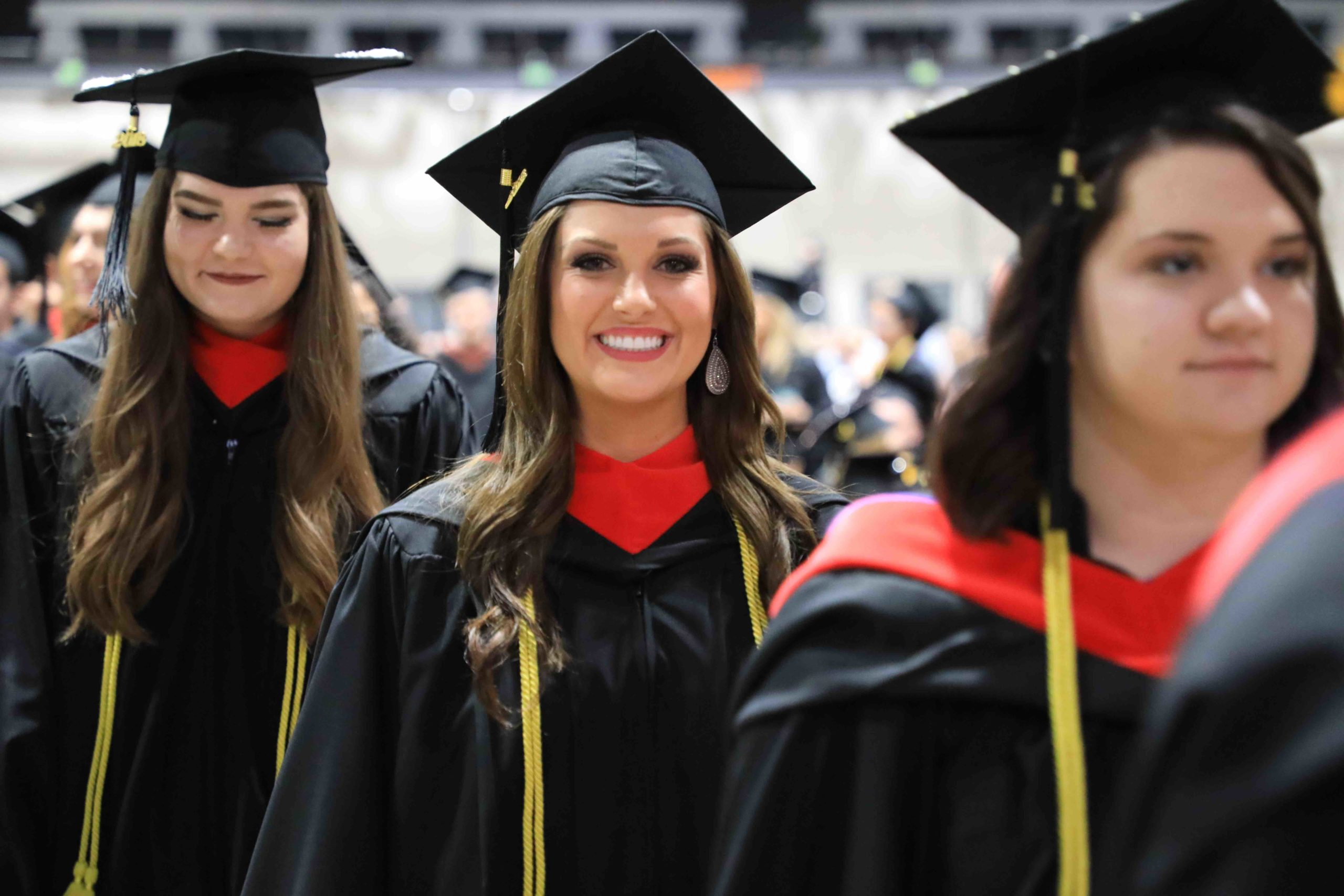 Female student smiles at the camera while standing in a line of three students wearing caps and gowns