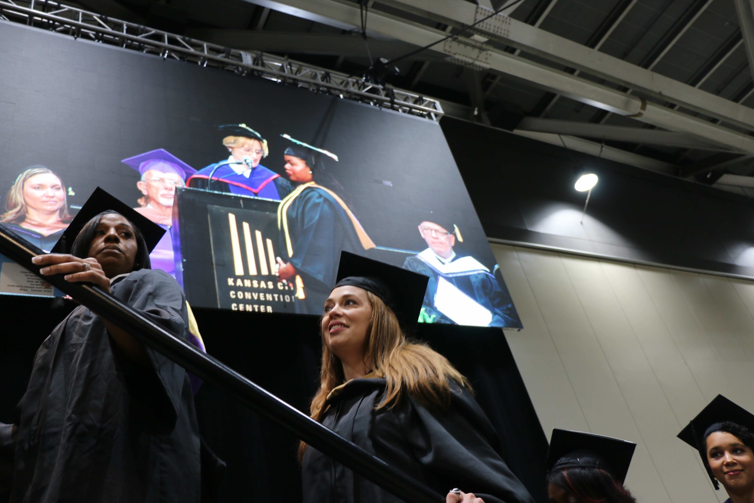 Two female students head up the stairs to the graduation stage wearing their caps and gowns