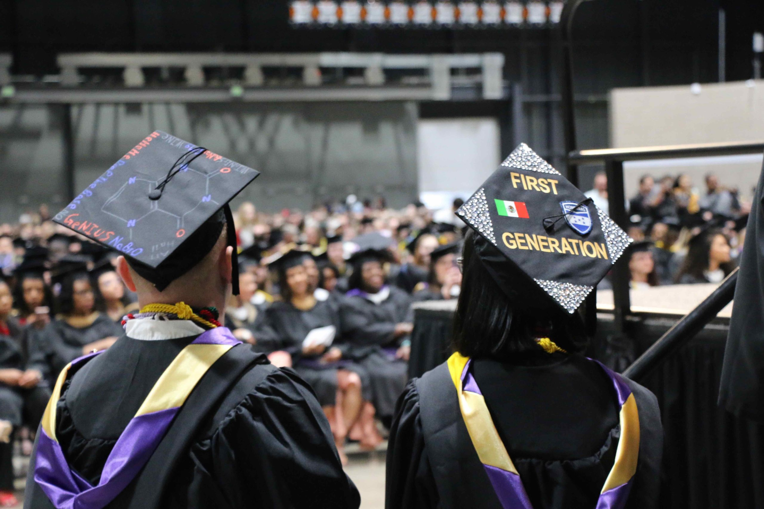 "Student looking at the crowd of graduates in their caps and gowns. Her cap reads ""First Generation"""