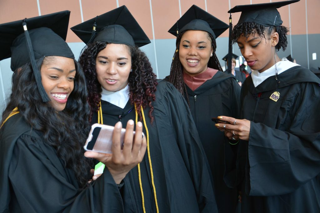 Four students stand together taking selfies in their caps and gowns
