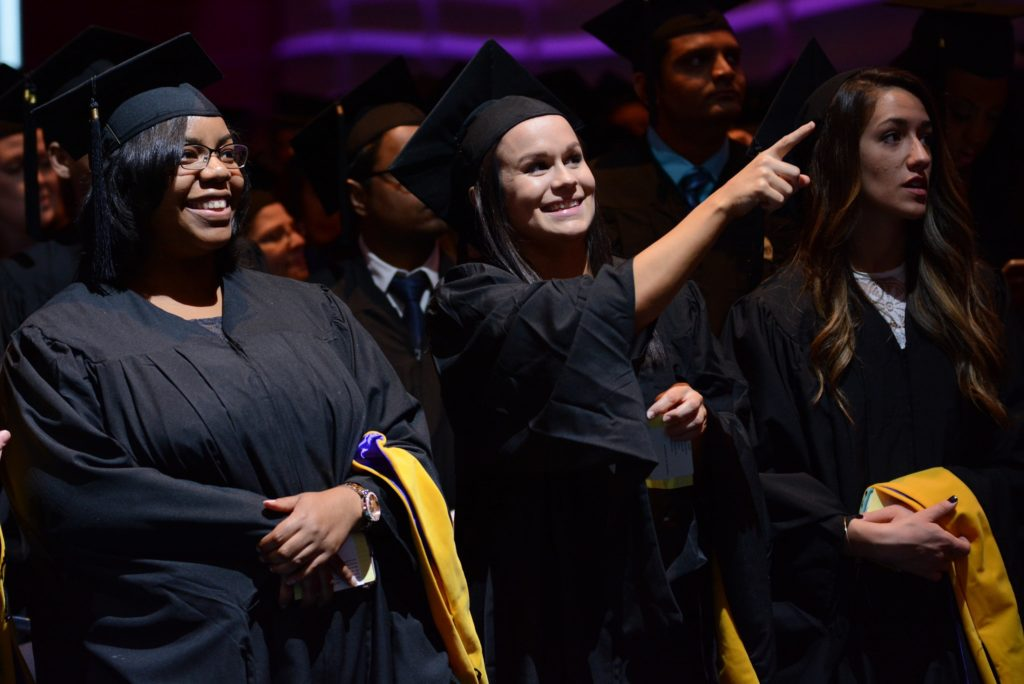 Three students point at the graduation stage while standing in the crowd wearing their caps and gowns.