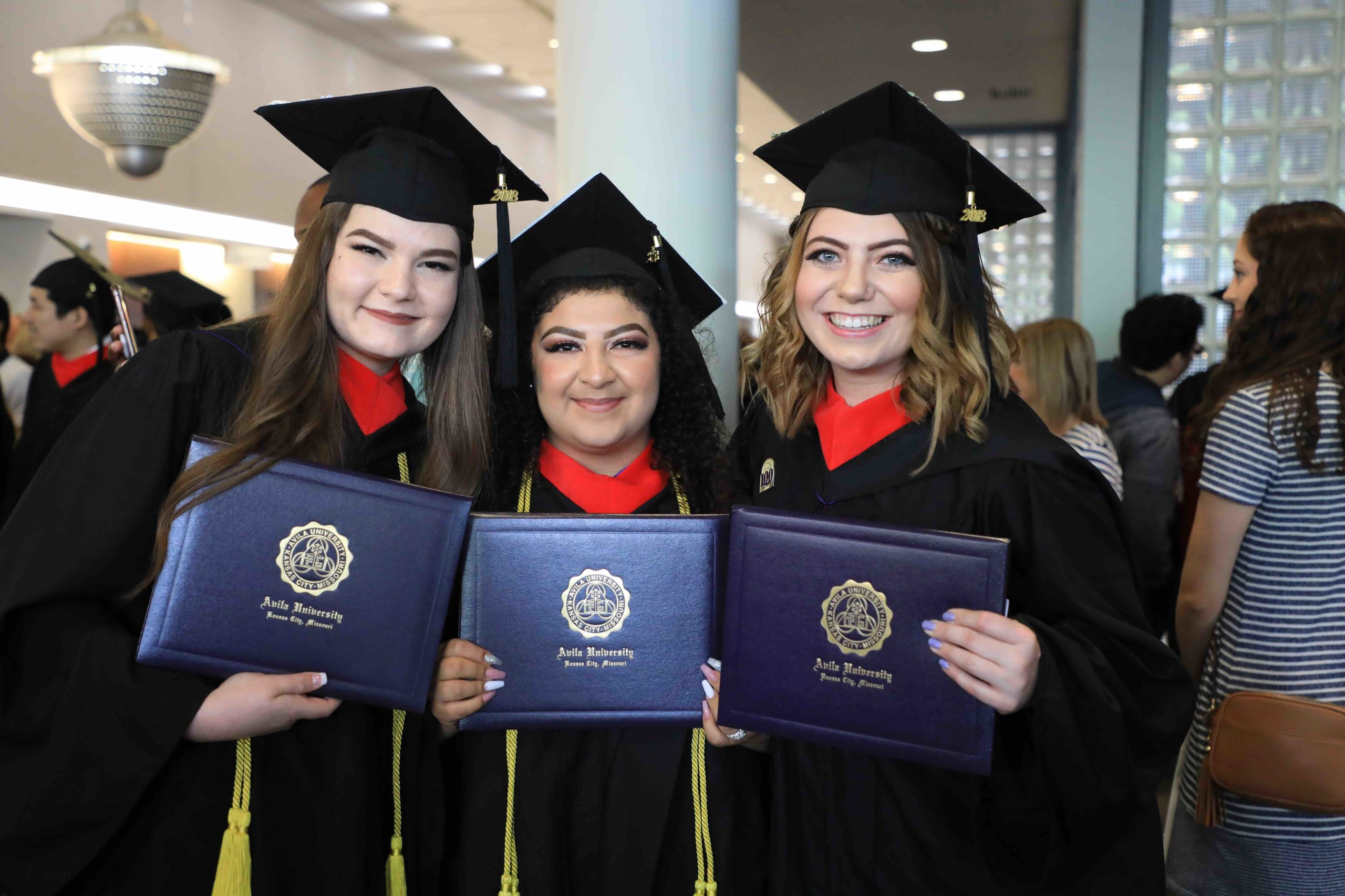 A group of three women posing with the diplomas at graduation in their caps and gowns