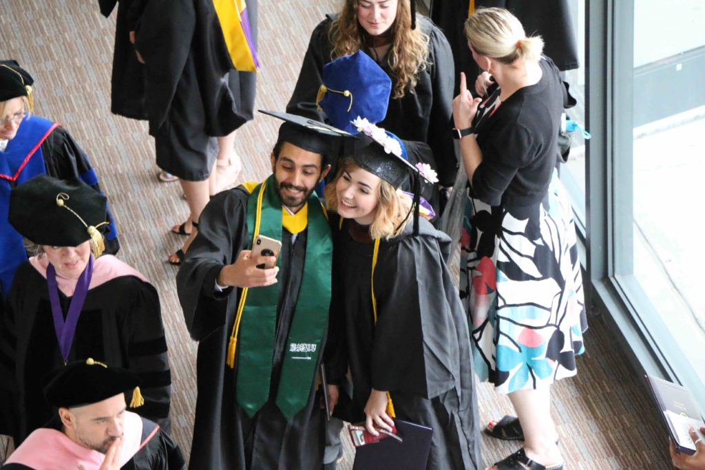 An overhead view of two graduates taking a selfie in their caps and gowns