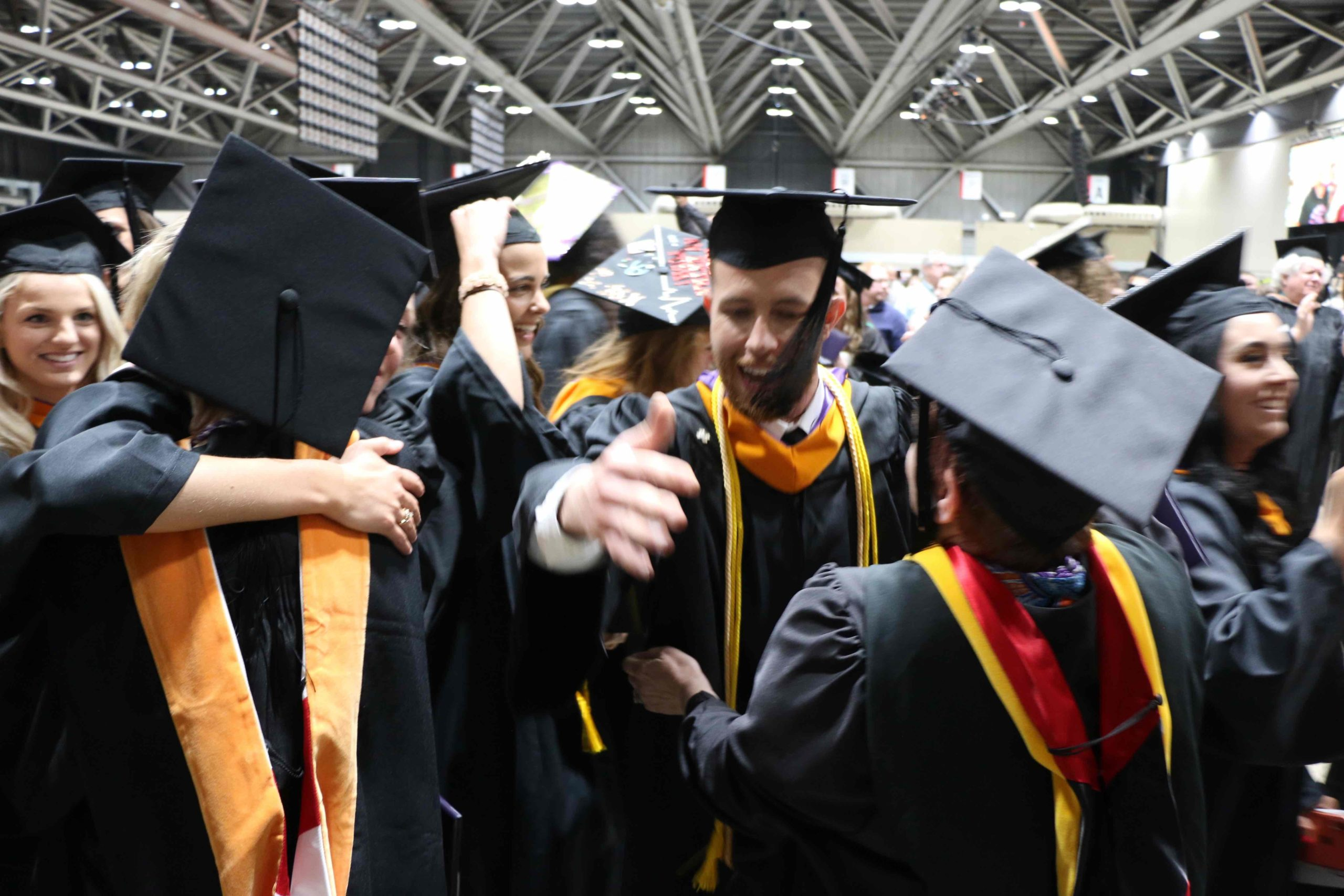 A group of students hugging in the reception line post-graduation