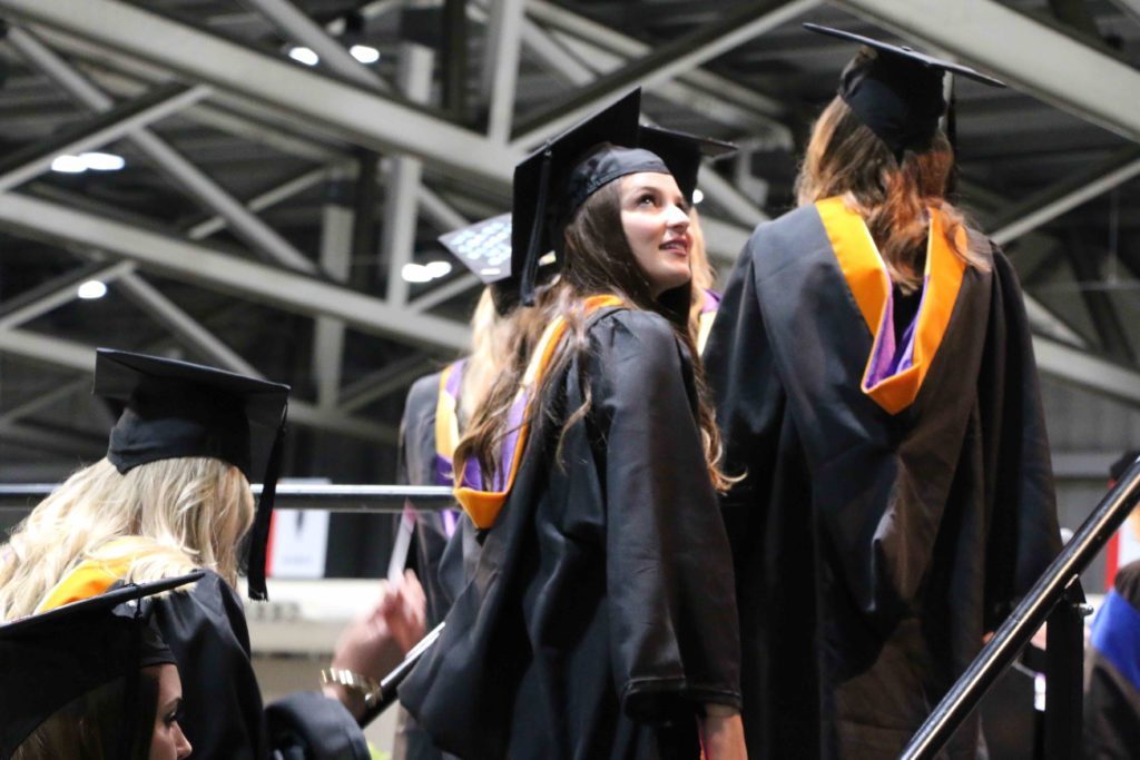 A graduate looks over her shoulder as she walks up the stairs to the commencement stage