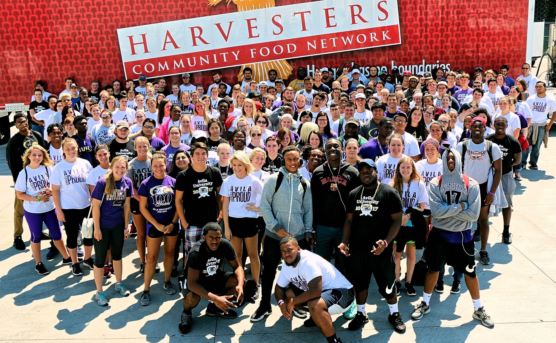 Large group of first year students standing in front of a Harvesters Community Food Network semi-trailer.