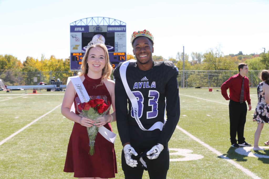 Homecoming Queen and King posing on the football field during halftime