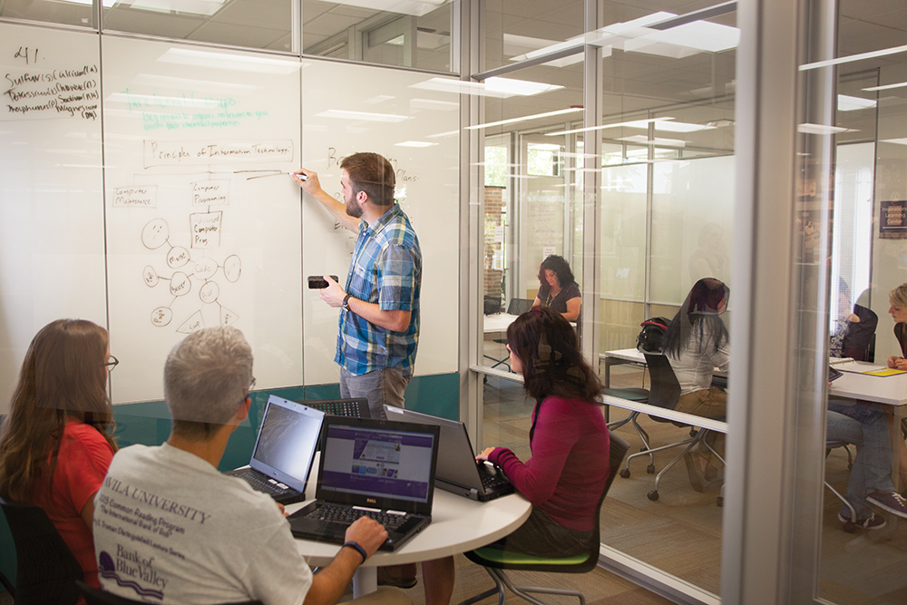 Adult students inside the Learning Commons with a whiteboard behind