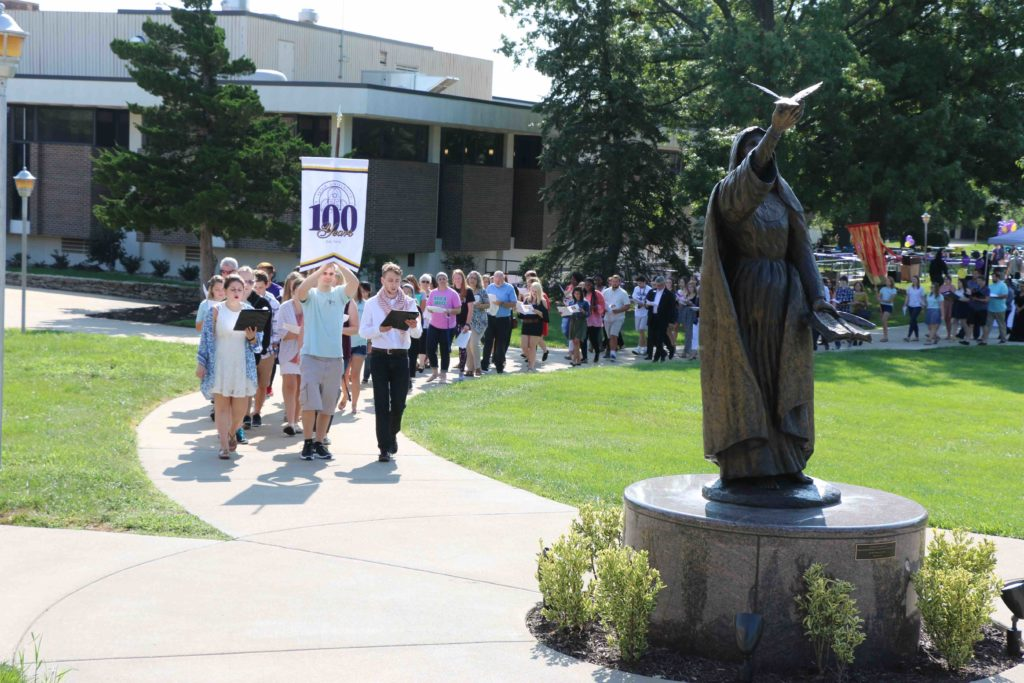 The Avila community marches across campus together in a long line promoting peace.