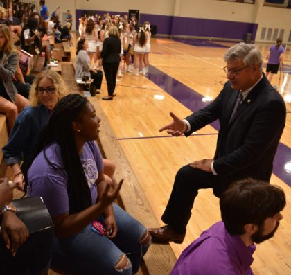 President Ronald Slepitza talks with students on the bleachers of Mabee Fieldhouse